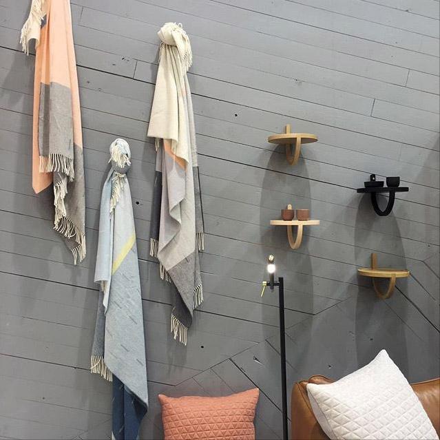 Vägghyllar på trävägg i grå färg. Textilier och kuddar.