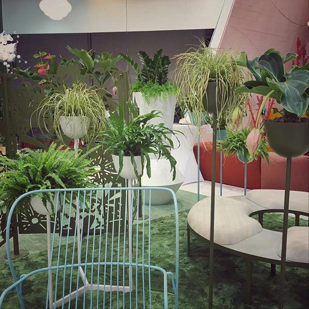 Gröna växter på grön matta i utställning om svensk design, mode och möbler.