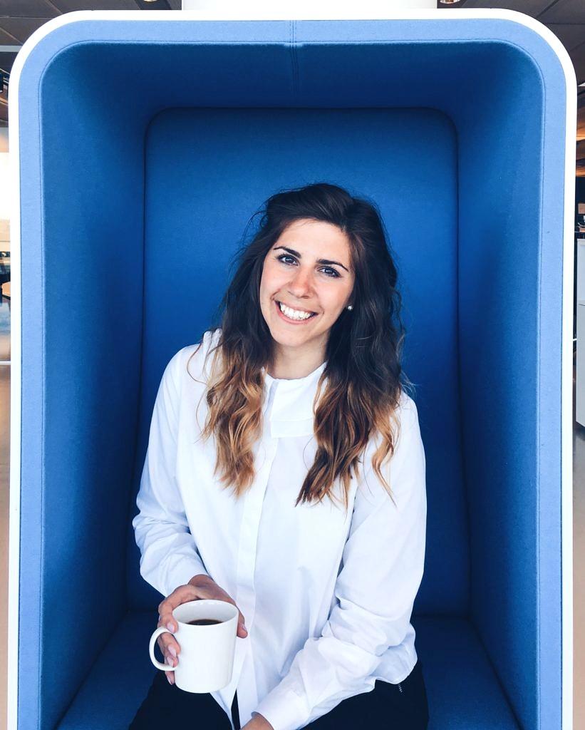 Kvinna i blå fåtölj med kaffekopp i handen.