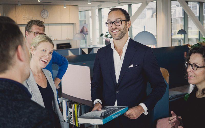 Man i blå kostym som håller i bok om arkitekten Ivar Tengbom. Människor i kontorslandskap.
